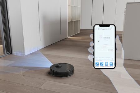 Auf einem Smartphone ist die Karte einer Wohnung aufgerufen. Im Hintergrund navigiert der DEEBOT T9 AIVI durch ein Zimmer. Blaue Lichtstrahlen zeigen dabei den kegelförmigen Bereich vor dem Roboter an, den dieser mittels KI auf Hinternisse absucht.
