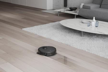 Der DEEBOT T9 AIVI wischt über Holzboden. Im Hintergrund stehen ein Sofa und zwei Tische auf einem Teppich.
